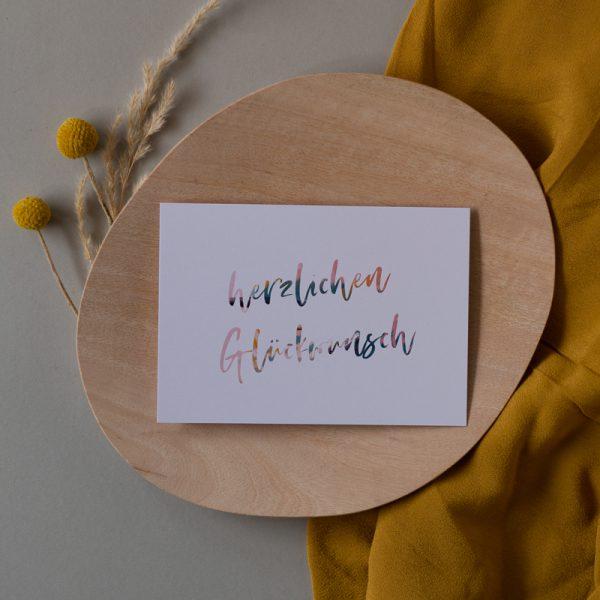 Herzlichen Glückwunsch Karte liegt auf Holzteller mit Trockenblumen