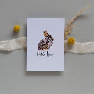 Osterkarte mit Hasen im Leopardenmuster liegt auf Seidenband und Trockenblumen